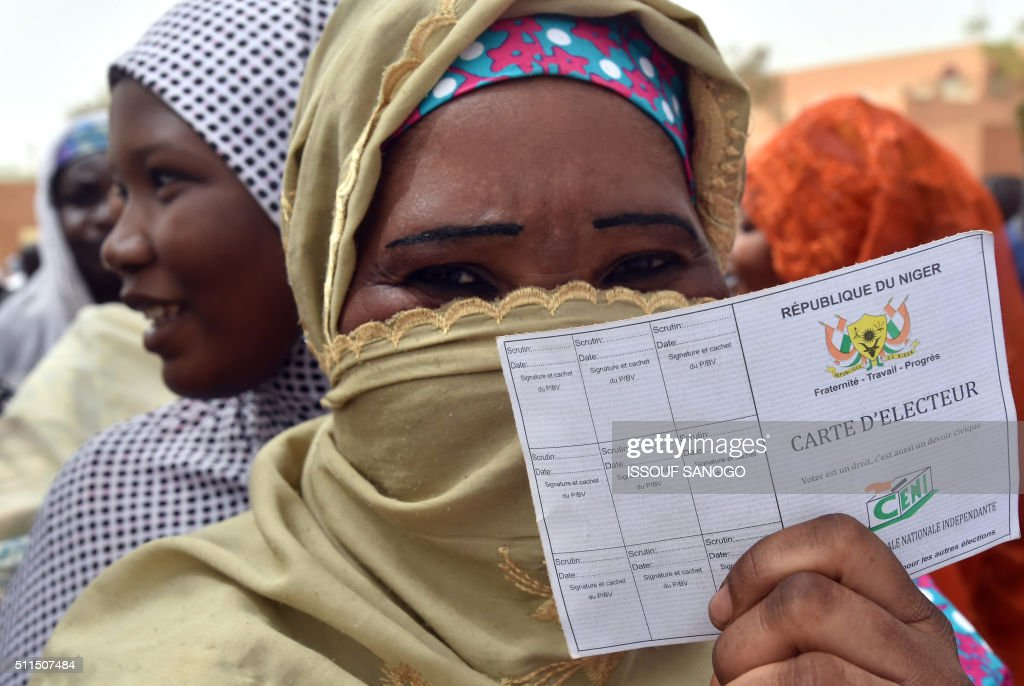 TOPSHOT - A woman queues with other voters outside a polling station in Niamey during the country's presidential and legislative elections on February 21, 2016. Voters in Niger went to the polls in an election in which President Mahamadou Issoufou has promised a 'knockout' blow to his opponents, one of whom is behind bars on baby-trafficking charges. / AFP / ISSOUF