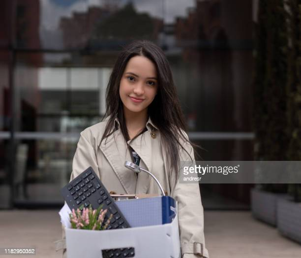 woman quitting her job and holding her belongings in a box - quitting a job stock pictures, royalty-free photos & images