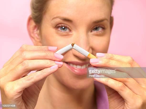 Woman quitting smoking by braking cigarette