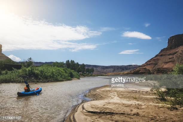 woman rafting with kayak in colorado river, moab - moab utah stock pictures, royalty-free photos & images