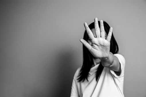 woman raised her hand for dissuade, campaign stop violence against women. Asian woman raised her hand for dissuade with copy space, black and white color 1001313596
