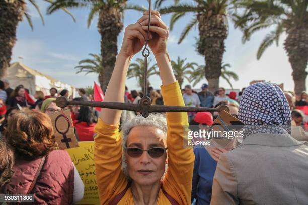 A woman raises a balance of gender equality during a march held in Tunis Tunisia to call for equal inheritance rights and gender equality on March 10...