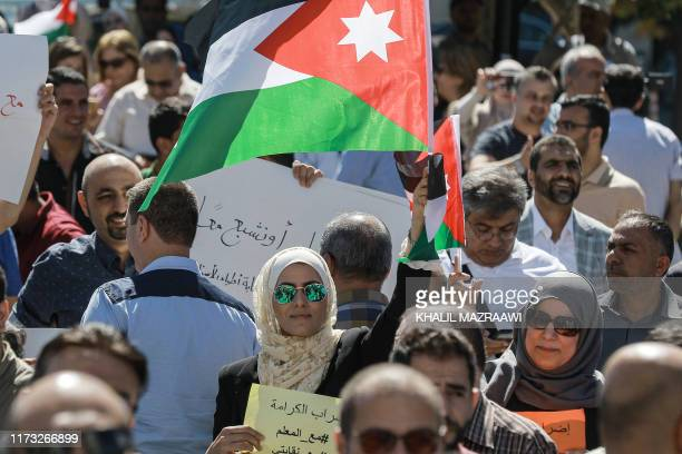 A woman raises a Jordanian national flag as she stands amidst public school teachers demonstrating and demanding pay raises at the Professional...