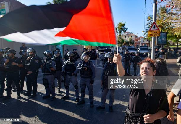 Woman raises a Palestinian flag in front of Israeli security forces standing guard, during a protest in the coastal city of Jaffa, near Tel Aviv, on...