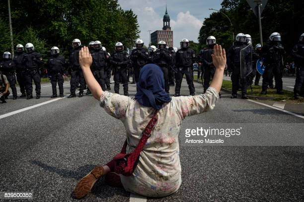 A woman raises hands in front of the police during demonstration against the g20 summit in Hamburg Germany on July 7 2017 German police and...