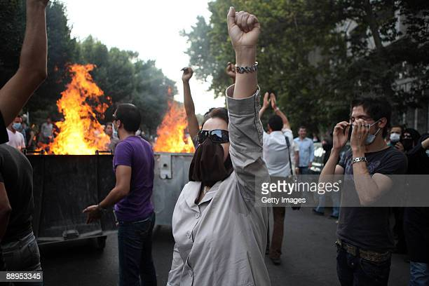 A woman raises her arm in protest as demonstrators burn rubbish in the street on July 9 2009 in Tehran Iran Following recent unrest in the wake of...