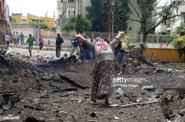 Woman raises her arms and shouts as she stands on the site where car bombs exploded on May 11, 2013 near the town hall of Reyhanli, just a few...
