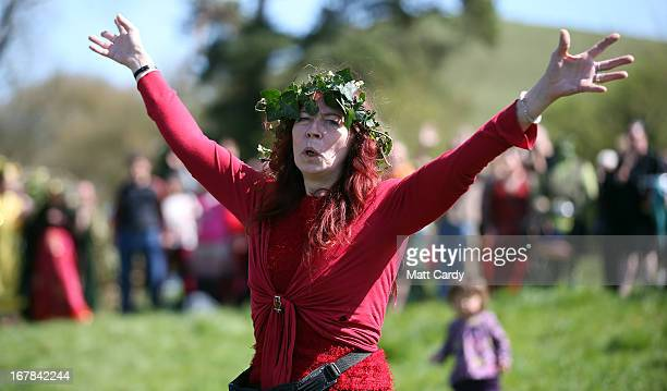 A woman raises her arms as she takes part in a Beltane May Day celebration below Glastonbury Tor on May 1 2013 in Glastonbury England Although more...