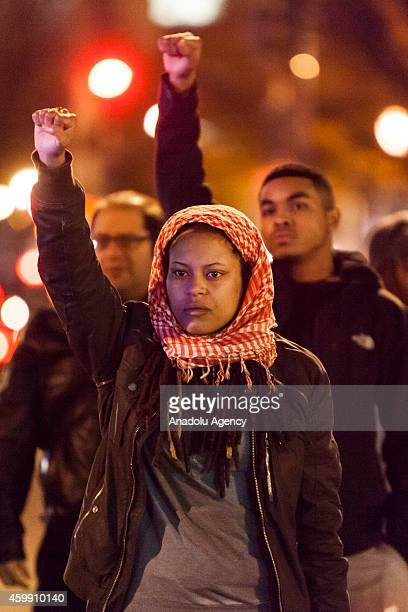 Woman raises her fist and chants during a protest after two grand juries decided not to indict the police officers involved in the deaths of Michael...