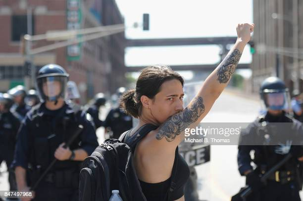 A woman raises her fist as she approaches a line of police officers in riot gear during a protest action following a not guilty verdict on September...