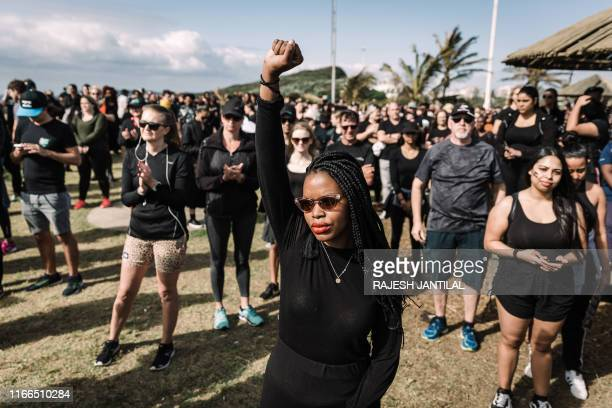 Woman raises her fist as she take part in a march against gender based violence and in solidarity with women who have been subject to violence and in...