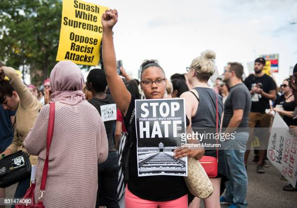 A woman raises her fist at the front of a march down Washington Avenue to protest racism and the violence over the weekend in Charlottesville...