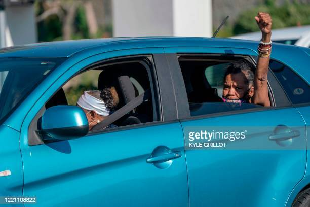 Woman raises her fist from a car as protesters march by during a Juneteenth demonstration over the death of Robert Fuller, in Lancaster, California,...