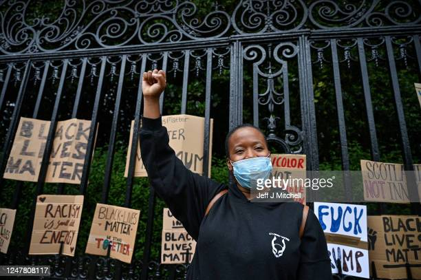 Woman raises her fist in the air as Black Lives Matter protesters hang their banners on the fence of Holyrood Palace, despite a call by First...