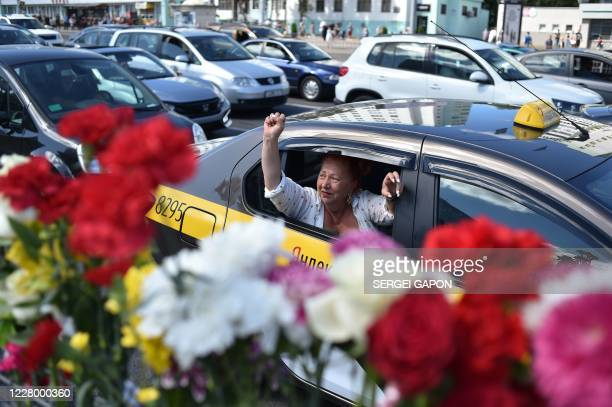 Woman raises her fist while riding in a taxi past the site where a protester died last night in Minsk on August 11, 2020. - The main challenger in...