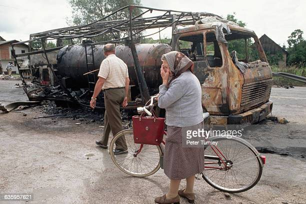A woman raises her hand to her face as she walks past the burntout shell of a truck evidence of a battle between the Slovenian Federal Army and...