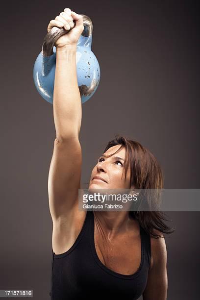 Woman Raising a Blue Kettle Bell