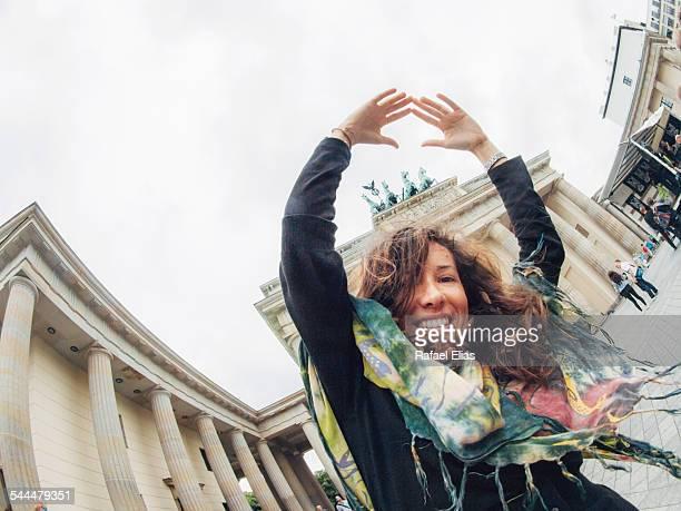 Woman raising arms by Brandenburg Gate in Berlin