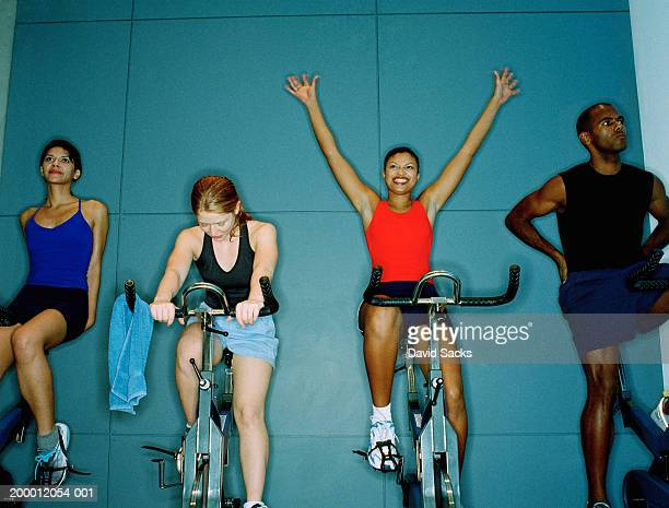 Woman raising arms on exercise bikes in gym