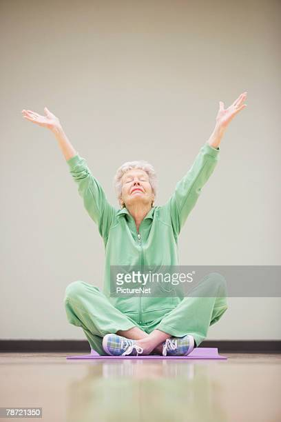 Woman Raising Arms on Exercise Mat