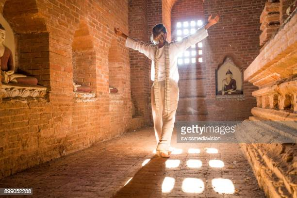 Woman raising arms to the sunlight, inside ancient temple