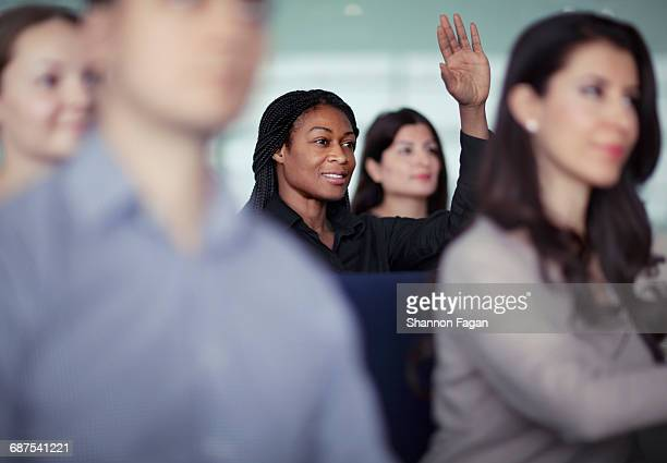 woman raising hand in group seminar workshop - education stock pictures, royalty-free photos & images