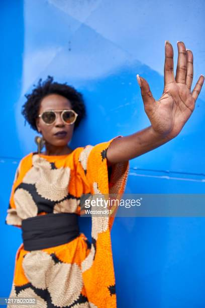woman raising her hand in front of blue background - request stock pictures, royalty-free photos & images