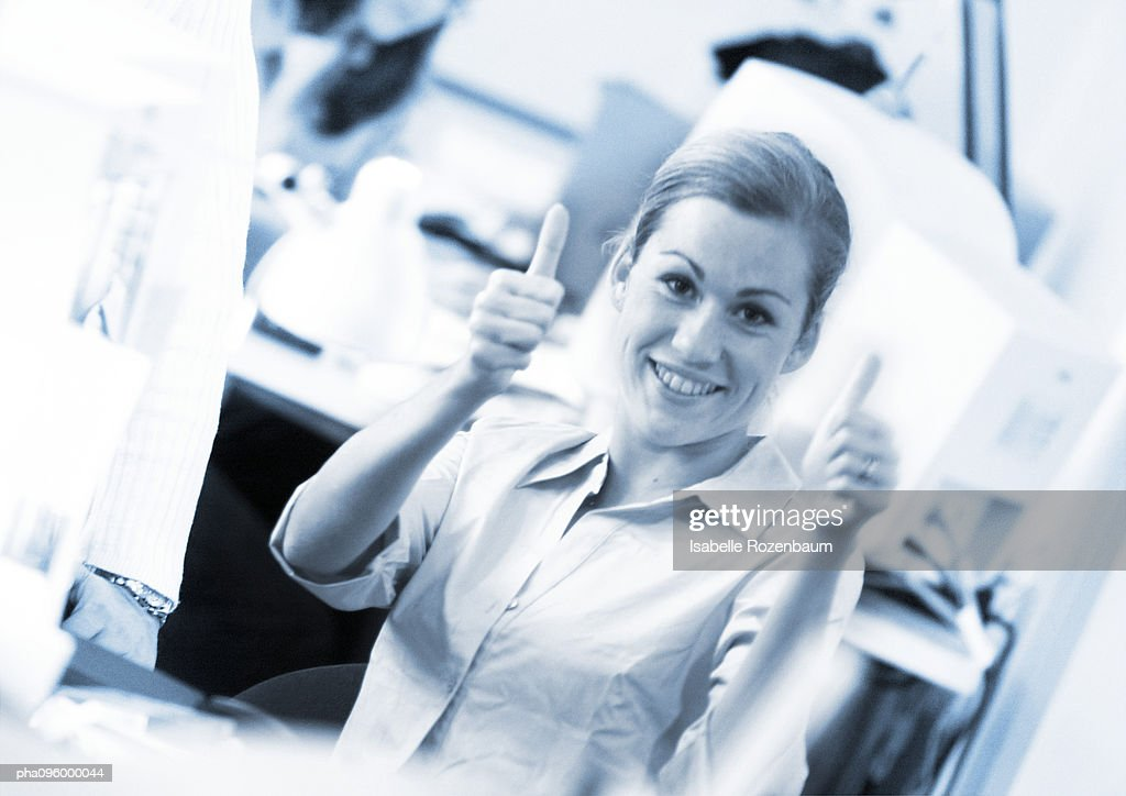 Woman raising thumbs, close-up, portrait : Stock Photo