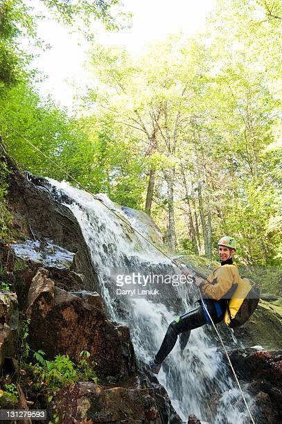 Woman rapelling down waterfall in forest