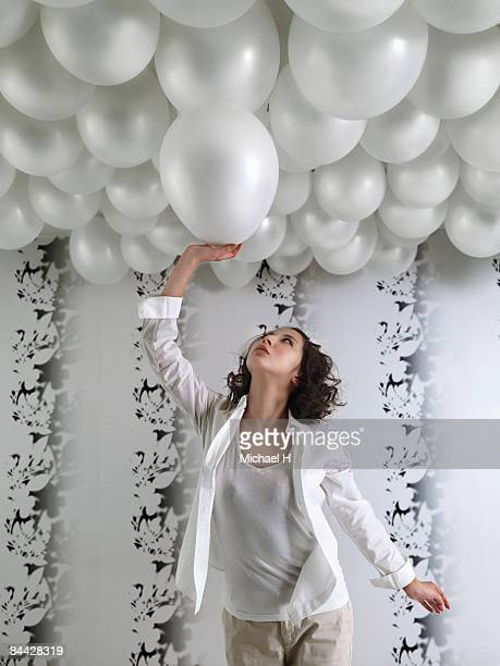 Woman reaches balloon that floats up and takes it