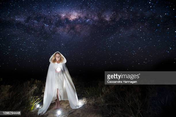 a woman reaches for and holds the stars - deus imagens e fotografias de stock