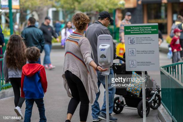 A woman reaches for hand sanitizer in Downtown Disney District shopping mall which remains open on the first day of the closure of Disneyland and...