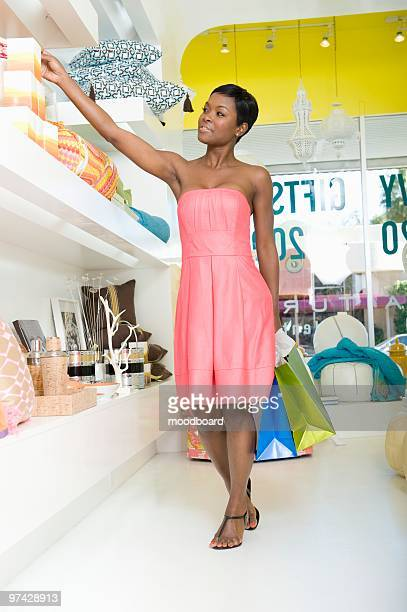 Woman reaches for product in home interiors store