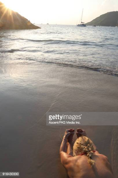Woman reaches for toes while relaxing on beach, sunrise