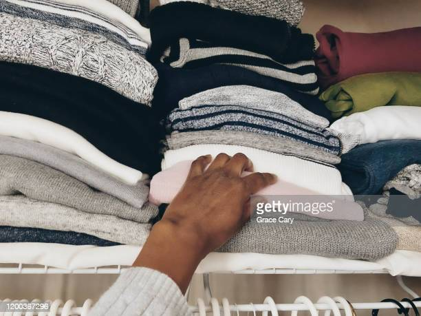 woman reaches on top shelf in closet - tidy room stock pictures, royalty-free photos & images
