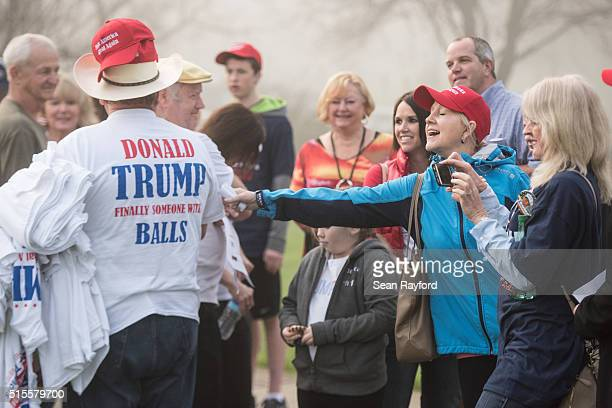A woman reaches out to a man peddling Donald Trump apparel before a campaign rally for the Republican presidential candidate at LenoirRhyne...