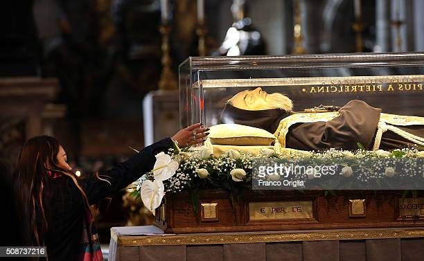 A woman reaches towards the corpse and relics of Padre Pio on display in St Peter's Basilica for veneration by the faithful in connection with the...