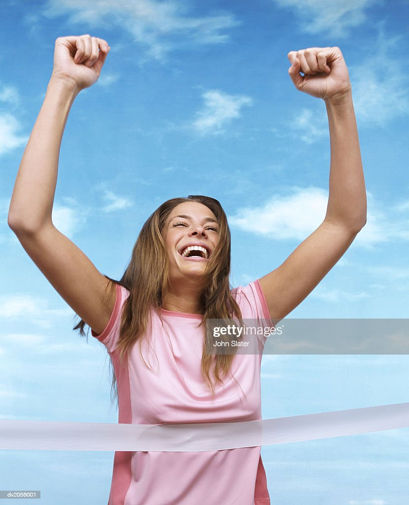 Woman Reaching a Finishing Line, with Her Arms Raised in Success : Stock Photo