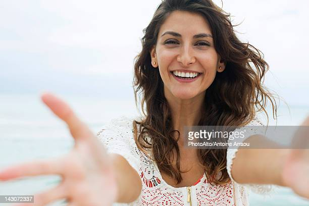 woman reaching arms toward camera, smiling - arms outstretched stock pictures, royalty-free photos & images