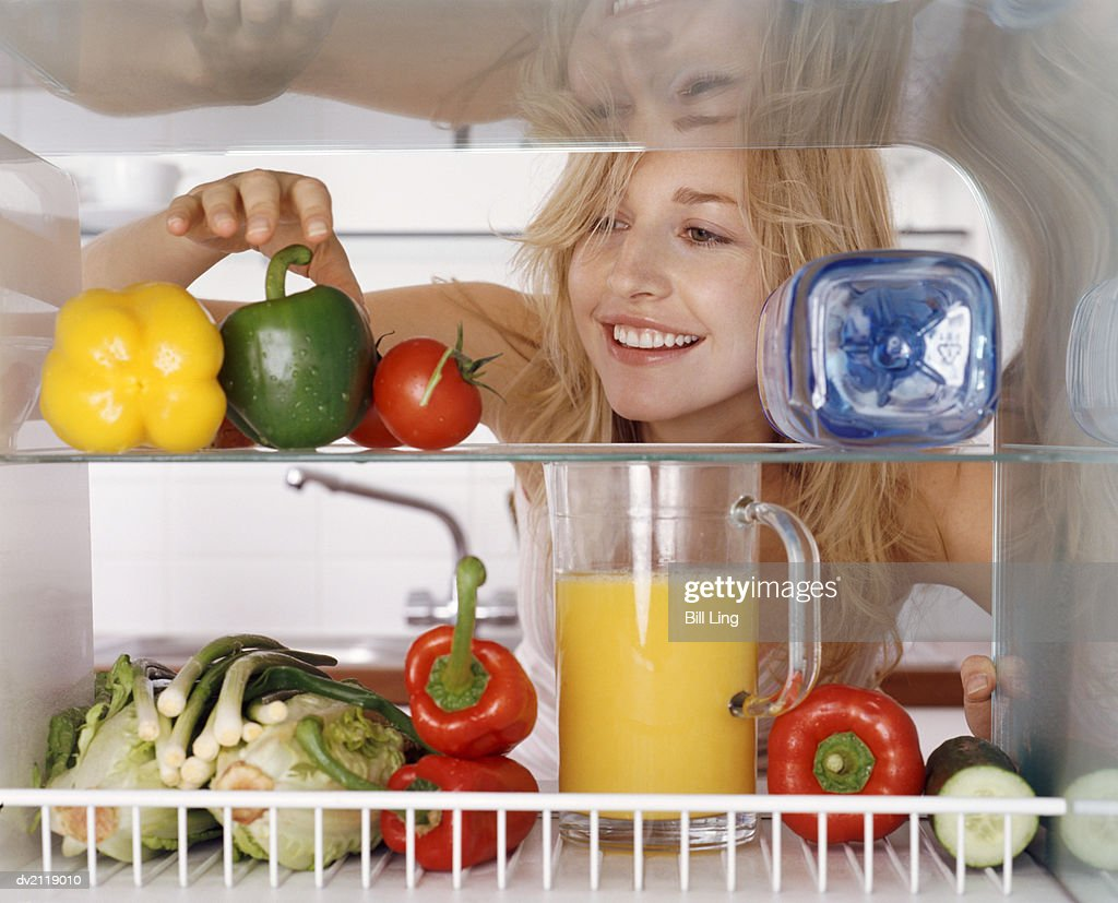 Woman Reaching for a Green Pepper in a Fridge : Stock Photo