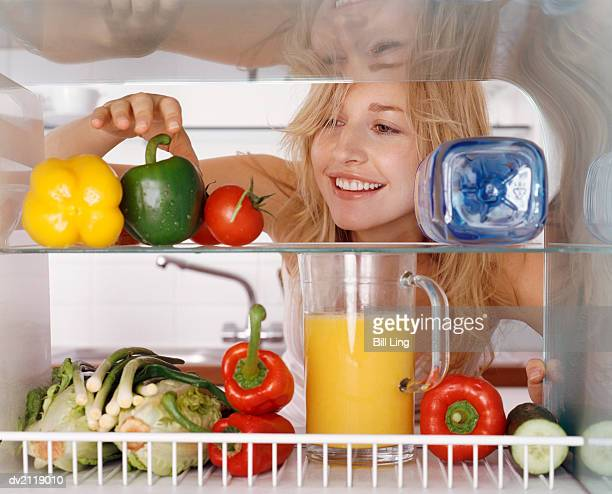 Woman Reaching for a Green Pepper in a Fridge