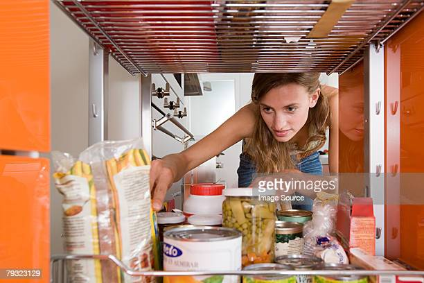 a woman reaching for a packet of food - cuisine non professionnelle photos et images de collection