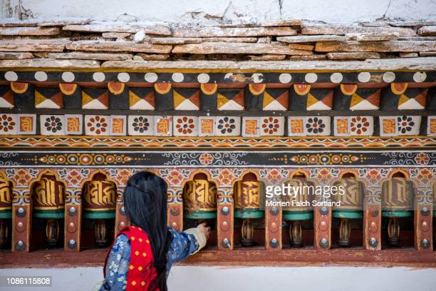 a woman reaching for a prayer bell - paro stock photos and pictures