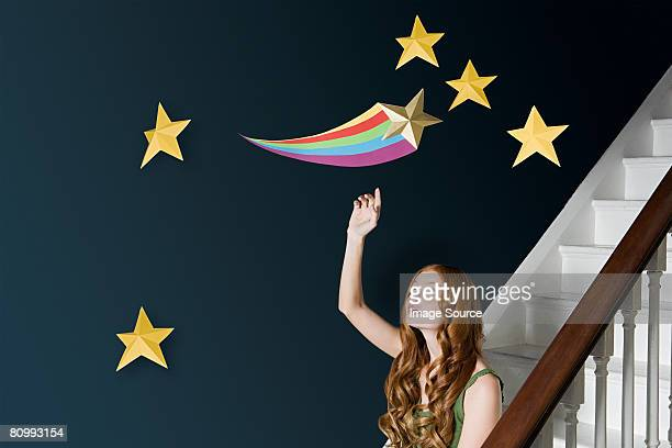 A woman reaching for a shooting star