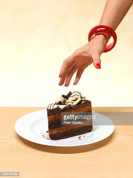 woman reaching for a slice of cake - reaching stock pictures, royalty-free photos & images