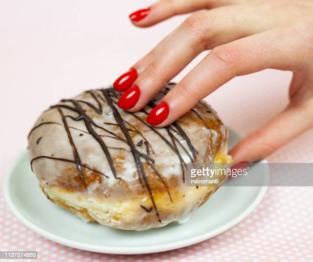 woman reaching for a sweet donut - red nail polish stock pictures, royalty-free photos & images