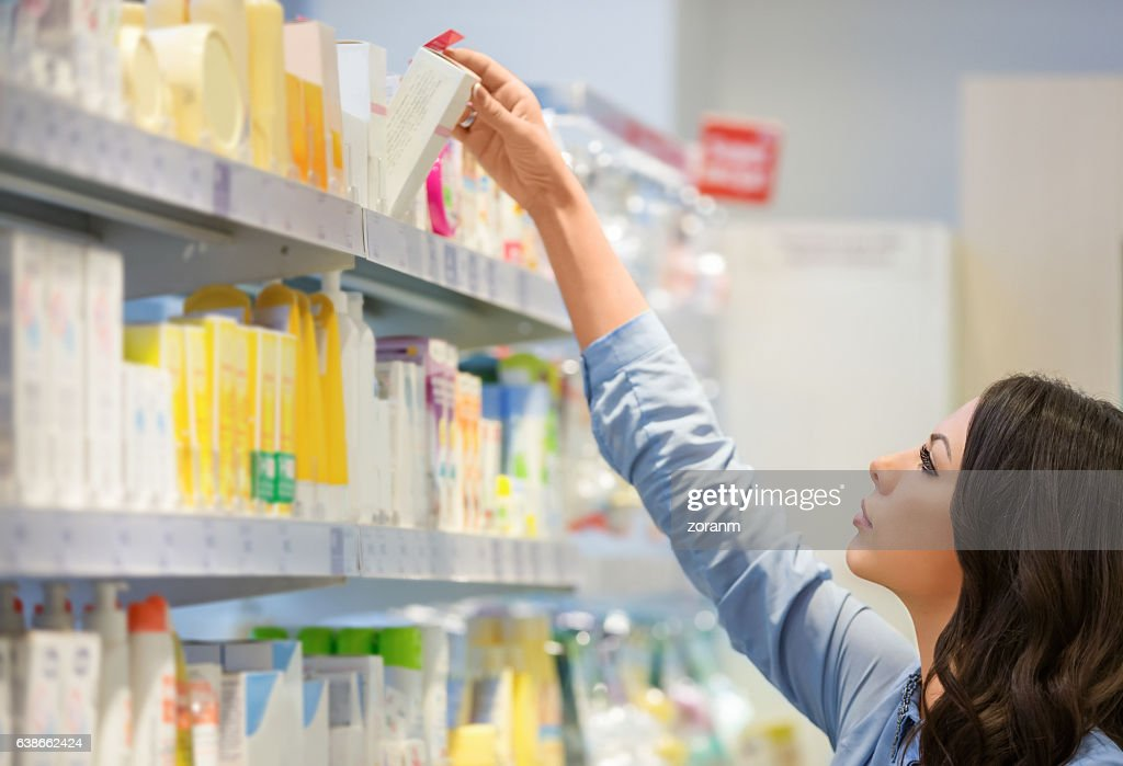 Woman reaching for beauty products : Stock Photo