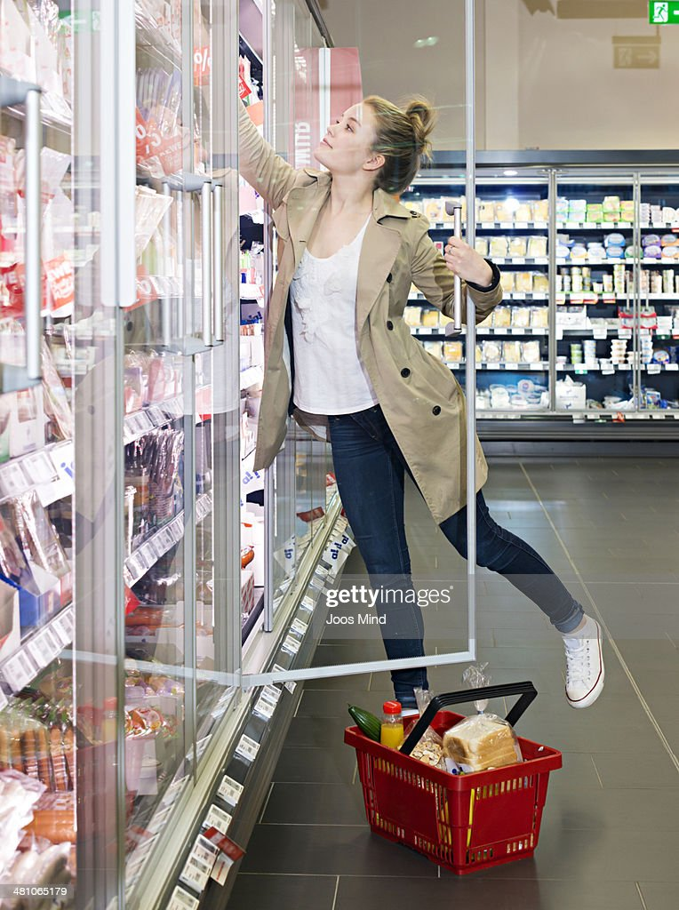woman reaching for diary produce in supermarket : Foto de stock