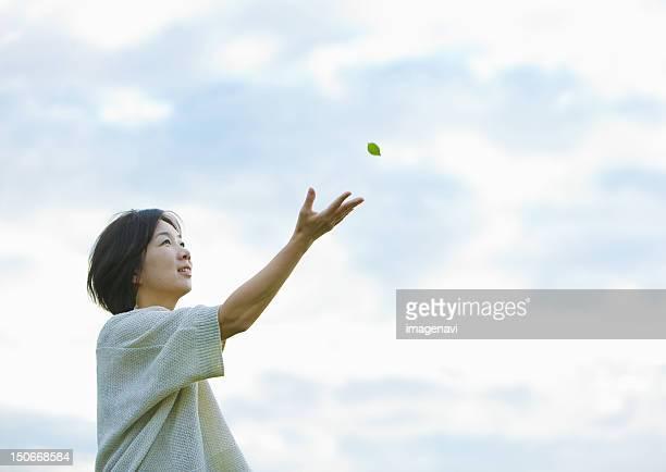 woman reaching for leaf - 手を伸ばす ストックフォトと画像