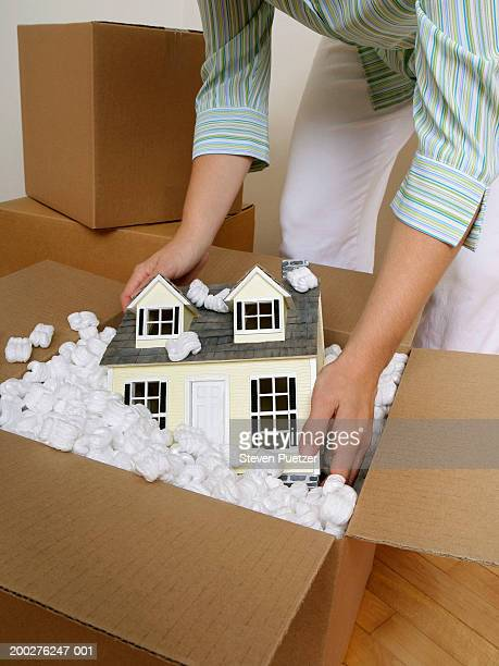 Woman reaching for model home in moving box